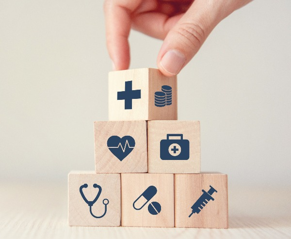 An image of blocks being stacked together to represent the many components of healthcare.
