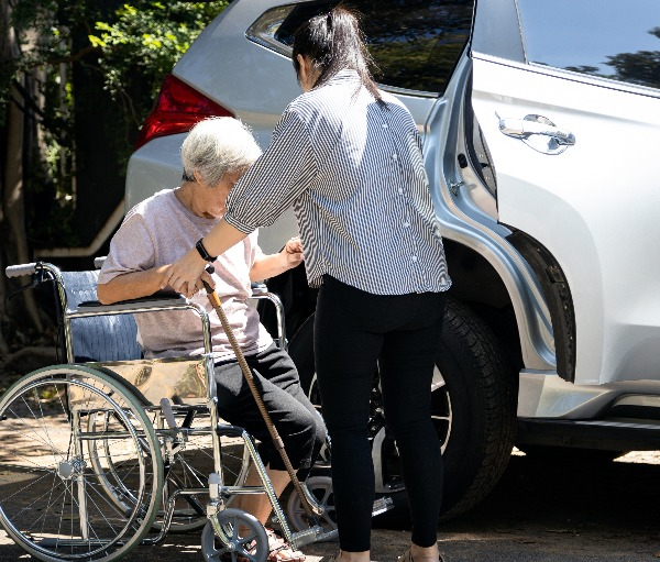 Woman helping older lady into vehicle from wheelchair.